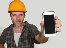 Trabajador del constructor en el casco del contratista que sostiene el edificio de ofrecimiento de la compañía del teléfono móvil imagenes de archivo