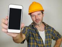 Trabajador del constructor en el casco del contratista que sostiene el edificio de ofrecimiento de la compañía del teléfono móvil imagen de archivo