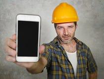 Trabajador del constructor en el casco del contratista que sostiene el edificio de ofrecimiento de la compañía del teléfono móvil fotografía de archivo libre de regalías