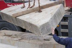 Trabajador del constructor que lleva a cabo perfil concreto durante la elevación de la grúa Imagenes de archivo