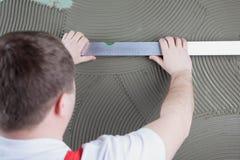 Trabajador del constructor que mide llano de la construcción de la pared con el special Foto de archivo libre de regalías