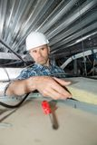 Trabajador del constructor del Roofer que instala el material de aislamiento del tejado fotos de archivo libres de regalías