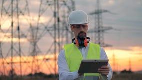 Trabajador del electricista con la tableta cerca de la línea eléctrica metrajes