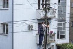 Trabajador del electricista en sistema eléctrico de la reparación de la escalera en pilar de la electricidad o polo para uso gene Fotos de archivo