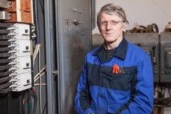 Trabajador del electricista que coloca el panel de alto voltaje cercano Imagen de archivo libre de regalías