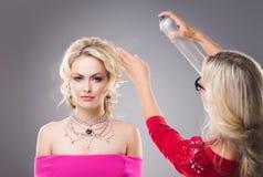 Trabajador del estudio que aplica una laca para el pelo sobre el pelo de blonde hermoso que lleva el vestido y el collar rosados Foto de archivo libre de regalías