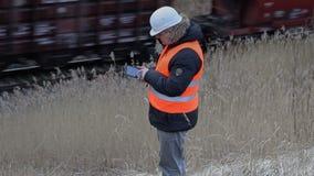 Trabajador del ferrocarril con la tableta cerca del ferrocarril almacen de metraje de vídeo