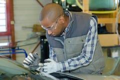 Trabajador del garaje que cabe el nuevo parabrisas fotografía de archivo