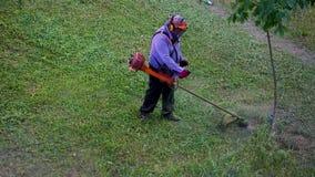 Trabajador del hombre del lawnmover de la visión superior que corta la hierba seca con el cortacésped almacen de metraje de vídeo