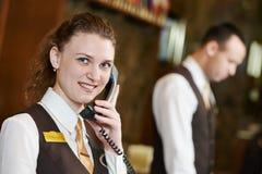 Trabajador del hotel con el teléfono en la recepción Imagen de archivo libre de regalías