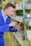 Trabajador del inventario en almacén Foto de archivo libre de regalías
