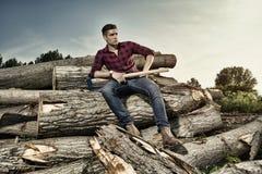 Trabajador del leñador que se sienta en el bosque Fotos de archivo