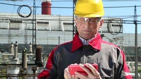 Trabajador del mantenimiento con smartphone rojo en la central eléctrica almacen de video