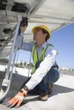 Trabajador del mantenimiento que instala los paneles fotovoltaicos solares Imagen de archivo libre de regalías