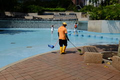 Trabajador del mantenimiento que limpia una piscina pública Imagen de archivo libre de regalías