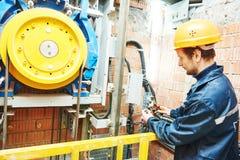 Trabajador del maquinista que ajusta el mecanismo del elevador de la elevación foto de archivo