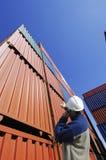 Trabajador del puerto y de muelle con los contenedores para mercancías Foto de archivo libre de regalías