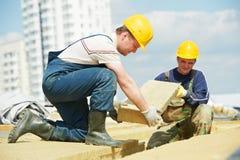 Trabajador del Roofer que instala el material de aislamiento del tejado