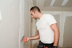 Trabajador del sector de la construcción con las herramientas que enyesa las paredes y que renueva la casa en emplazamiento de la Fotos de archivo libres de regalías