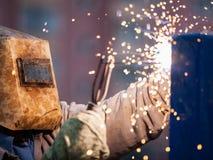 Trabajador del soldador del arco en la construcción metálica de la soldadura de la máscara protectora Fotografía de archivo libre de regalías