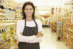 Trabajador del supermercado que se coloca en pasillo del ultramarinos imagen de archivo