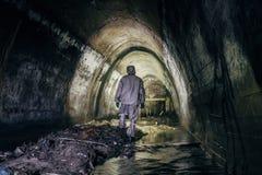 Trabajador del túnel de la alcantarilla en la habitación protectora química en túnel gaseoso subterráneo de la alcantarilla imágenes de archivo libres de regalías