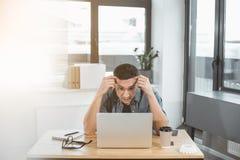 Trabajador desengañado que mira en el ordenador portátil foto de archivo libre de regalías