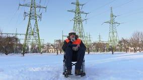 Trabajador discapacitado en la escritura de la silla de ruedas bajo líneas de alto voltaje metrajes