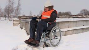 Trabajador discapacitado en la silla de ruedas que comprueba los materiales de construcción almacen de metraje de vídeo