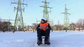 Trabajador discapacitado en la silla de ruedas usando la tableta cerca a las líneas de alto voltaje metrajes