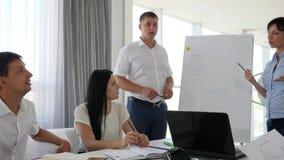Trabajador dos al lado del whiteboard que discute el desarrollo de negocios en forma del diagrama almacen de metraje de vídeo