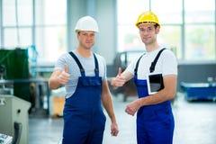 Trabajador dos en fábrica con el pulgar para arriba foto de archivo libre de regalías