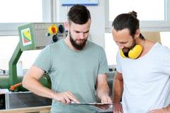 Trabajador dos en un taller del ` s del carpintero en la conversación fotografía de archivo libre de regalías