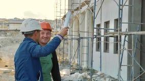 Trabajador e ingeniero de construcción que hablan en el sitio del emplazamiento de la obra Imagen de archivo libre de regalías