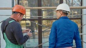 Trabajador e ingeniero de construcción que hablan en el sitio del emplazamiento de la obra, vista posterior Imágenes de archivo libres de regalías
