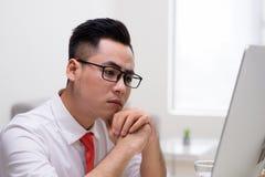 Trabajador elegante joven en la oficina que trabaja con el ordenador y el thinkin foto de archivo