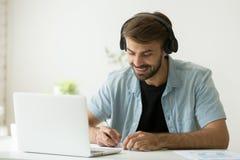 Trabajador en auriculares que escucha la escritura audio del curso importante imagen de archivo