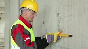 Trabajador en casco amarillo con el nivel en el solar almacen de metraje de vídeo