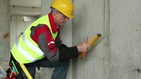 Trabajador en casco amarillo con el nivel en el terreno edificable almacen de video