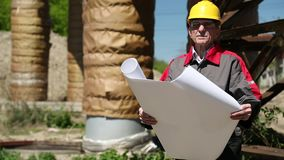 Trabajador en casco amarillo con los dibujos de estudio en la estación del calor almacen de metraje de vídeo
