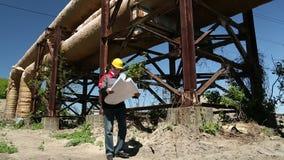Trabajador en casco amarillo con los dibujos del proyecto en la central eléctrica del calor almacen de video
