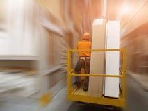 Trabajador en casco con el cinturón de seguridad en la carretilla elevadora con las mercancías en supermercado del edificio grand imagen de archivo libre de regalías