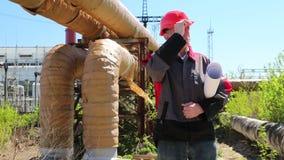 Trabajador en casco rojo con los dibujos de estudio en la estación del calor metrajes