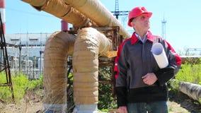 Trabajador en casco rojo con los dibujos de estudio en la estación del calor almacen de video