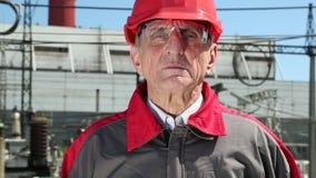 Trabajador en casco rojo en la central nuclear que mira la cámara metrajes