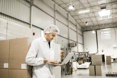 Trabajador en el almacén para el acondicionamiento de los alimentos Imagen de archivo libre de regalías