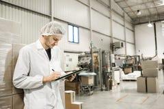 Trabajador en el almacén para el acondicionamiento de los alimentos Imágenes de archivo libres de regalías