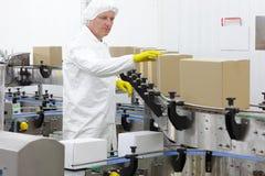 Trabajador en el delantal, casquillo en la cadena de producción en fábrica Fotografía de archivo