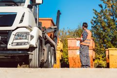 Trabajador en el emplazamiento de la obra que descarga el envase para la basura del camión foto de archivo