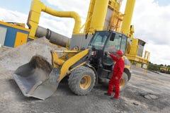 Trabajador en entrar uniforme del rojo al buldozer en el emplazamiento de la obra fotos de archivo libres de regalías